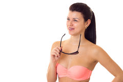 Woman in swimming suit with sunglasses. Charming young woman with long ponytail in pink bra with black sunglasses on white background in studio Royalty Free Stock Photos