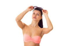Woman in swimming suit with sunglasses. Gorgeous young woman with long ponytail in pink bra with black sunglasses on white background in studio Stock Photos