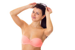 Woman in swimming suit with sunglasses. Young attractive woman with long ponytail in pink bra with black sunglasses on white background in studio Stock Photos