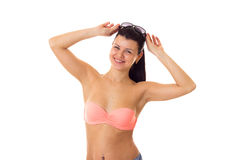 Woman in swimming suit with sunglasses. Young attractive woman with ponytail in pink bra and denim shorts with black sunglasses on white background in studio Stock Photo