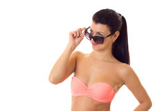Woman in swimming suit with sunglasses. Young beautiful woman with long ponytail in pink bra with black sunglasses on white background in studio Stock Image