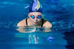 Woman swimming with swimming hat in swimming pool stock photo