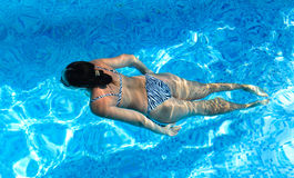 Woman swimming in a turquoise blue pool Royalty Free Stock Photography