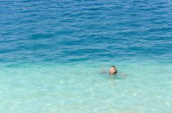 Woman swimming in the turquoise crystal clear sea. In Greece Stock Photos