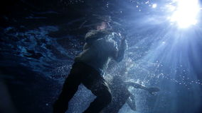 Woman swimming under water in long yellow dress. Underwater activity and woman swimming under water in clothes stock footage