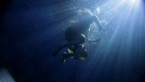 Woman swimming under water in long yellow dress. Underwater activity and woman swimming under water in clothes stock video footage