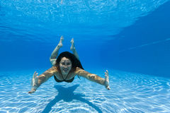 Woman swimming underwater in a pool stock image