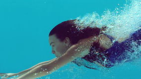 Woman swimming underwater. In slow motion stock video