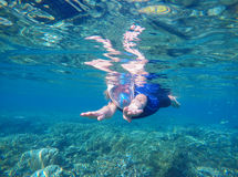 Woman swimming underwater in swimming costume and full-face mask Royalty Free Stock Images