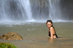 Woman swimming by waterfall Stock Images