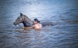Woman swimming winth her black stallion Royalty Free Stock Image