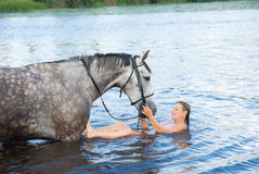 Woman swimming winth  stallion in river Royalty Free Stock Image