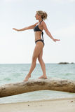 Woman in swimmsuit poises on wood trunk Royalty Free Stock Photos