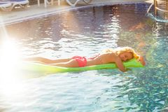 Woman swims with airbed. At the swimming pool in summer sunlight royalty free stock photo