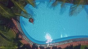 Woman swims on buoy in pool under excotic trees. Panoramic view tanned woman swims on buoy in long pool with sun rays reflection under excotic trees stock video footage