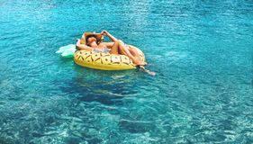 Woman swims on inflatable pineapple ring in the clear sea water. Summer sea vacation stock photography