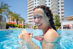 Woman swims in pool with glass of cocktail Royalty Free Stock Photos