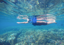Woman swims undersea in swimming costume and full-face mask. Stock Photo