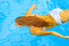 Woman swims underwater Stock Photo