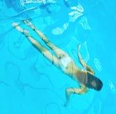 Woman swims underwater Stock Photo