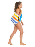 Woman in swimsuit with beach bag going sideways Stock Photos