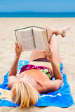 A woman in a swimsuit on a beach reading a book Royalty Free Stock Image