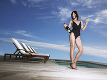Woman In Swimsuit With Champagne Bottle By Pool Stock Image