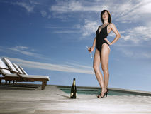Woman In Swimsuit With Champagne By Pool Stock Photo