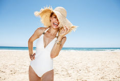 Woman in swimsuit hiding in big straw hat at sandy beach. Heading to white sand blue sea paradise. Smiling woman in white swimsuit hiding in big straw hat at Stock Photos