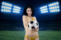 Woman in swimsuit holding ball at field. Portrait of sexy woman wearing bikini holding a soccer ball at field Stock Images