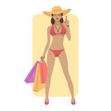 Woman in swimsuit holds phone and bags Royalty Free Stock Photo