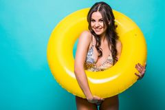 Young Woman in swimsuit inside inflatable ring isolated over green background. Woman in swimsuit inside inflatable ring isolated over green royalty free stock image
