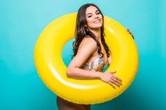Young Woman in swimsuit inside inflatable ring isolated over green background. Woman in swimsuit inside inflatable ring isolated over green stock photo
