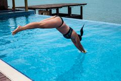 Girl jumping on swimming pool with Black sea view. Woman in swimsuit jumping on resorts pool stock image