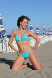 Woman in swimsuit kneeling on beach Royalty Free Stock Photo