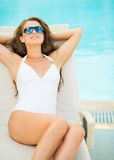 Woman in swimsuit laying on chaise-longue poolside. Young woman in swimsuit laying on chaise-longue poolside stock photography