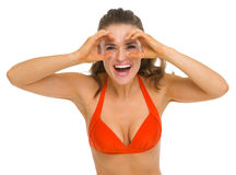 Woman in swimsuit looking through binoculars Royalty Free Stock Image