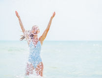 Woman in swimsuit playing with sea water Stock Images