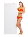 Woman in swimsuit pointing on blank billboard Royalty Free Stock Photos