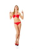 Woman in a swimsuit pointing on copy space Royalty Free Stock Image