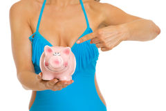 Woman in swimsuit pointing on piggy bank. Closeup Stock Photography