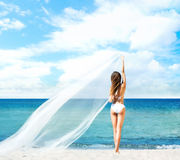 A woman in a swimsuit posing with a silk blanket Stock Images