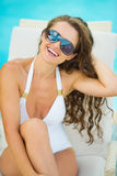 Woman in swimsuit relaxing on chaise-longue Stock Photo