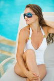 Woman in swimsuit relaxing on chaise-longue Royalty Free Stock Image