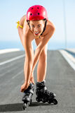 Woman in swimsuit with rollers on the highway Royalty Free Stock Photos