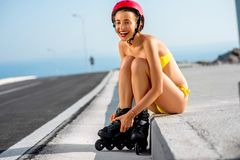 Woman in swimsuit with rollers on the highway Stock Photography