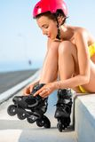 Woman in swimsuit with rollers on the highway Royalty Free Stock Images