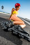Woman in swimsuit with rollers on the highway Stock Photo