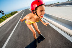 Woman in swimsuit with rollers on the highway Stock Image