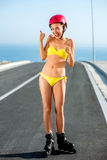 Woman in swimsuit with rollers on the highway Stock Photos
